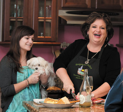 Photo by Judy Watson Tracy// Mayanne Downs' vivacious personality and cooking talents are showcased when throwing dinner parties, shown here happy in the kitchen with daughter Savannah and Daisy, a Maltese puppy.
