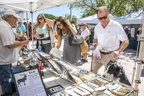 Photo by Mark Wallheiser. One of Suskauer's favorite weekend activities is to stroll through the West Palm Beach Green Market, where she purchases fresh produce for a variety of recipes. Accompanying her are Judge Scott Suskauer and the family dog, who also appears to enjoy the sunny weather and special goodies.