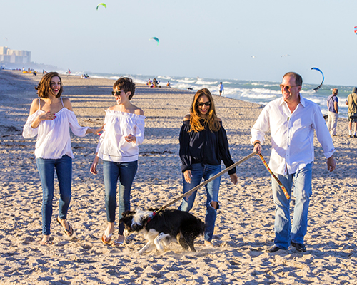 """Photo by Mark Wallheiser//Pictured from the left are Talia, Becca, Michelle, and Judge Scott Suskauer with the family border collie, Tucker, on the shores of Jupiter. The Suskauer daughters are talented musical theater artists. They are the first siblings to enter the prestigious program at Penn State University. """"Knowing that they are very self-possessed, happy, confident, and strong — I have done my job,"""" their mother said."""