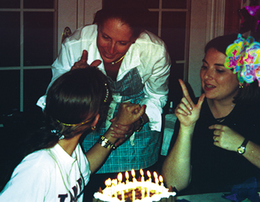 """Lindsay Lewis, celebrating her """"Sweet 16"""" birthday, communicates with tactile sign language using signs formed with her hands."""